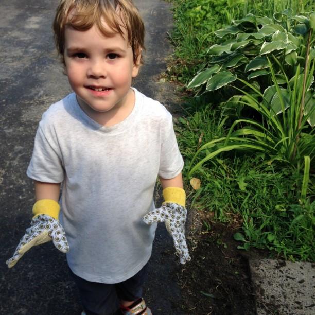 3 year old boy wearing gardening gloves and smiling